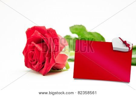 Red rose with stalk and leaves lying on surface against red card