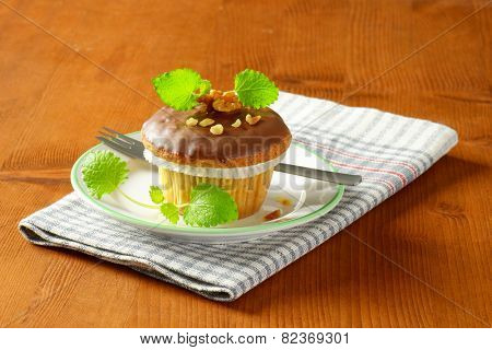 chocolate muffin and fork on white plate and checkered dishtowel