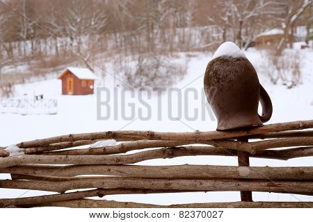 Clay pot on a wooden fence