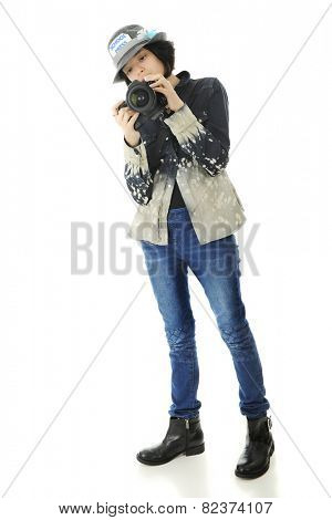 A young teen school photographer checking her camera setting before taking a shot.  On a white background.