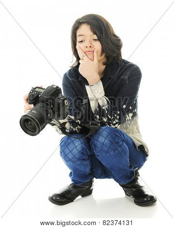 A young squatting photographer carefully studying the image in the back of her camera.  On a white background.