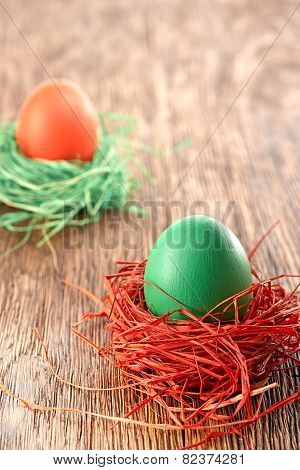 Painted Easter Eggs in colorful nests on wooden background