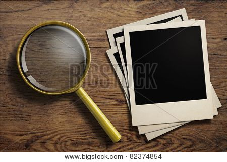 magnifying glass or loupe with old polaroid photo frames stack on wood table