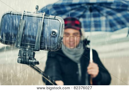 a young man taking a self-portrait with a selfie-stick under the rain
