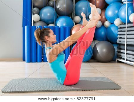 Pilates Open Leg Rocker exercise on mat woman with balls background gym