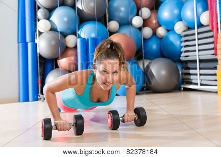 Girl at gym push-up strength pushup exercise with dumbbells workout