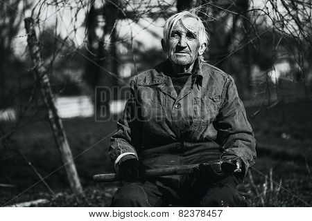 Black And White Grandfather Sitting Outdoors With Axe