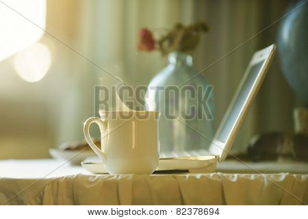 Cup with hot tea near computer