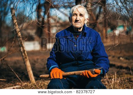 Grandfather In Blue Workwear Sitting Outdoors With Axe