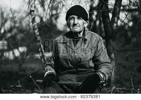 Monochrome Old Man In Workwear Sitting Outdoors