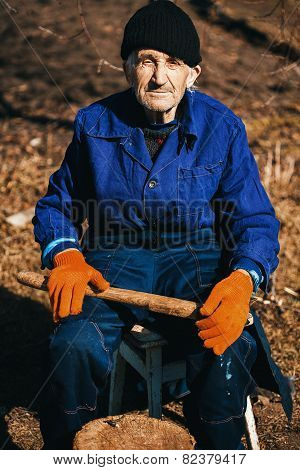 Old Man In Blue Workwear Sitting Outdoors With Axe