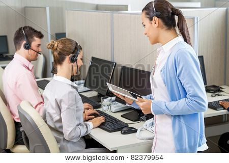 Female customer service executive holding digital tablet while talking to colleagues working in call center