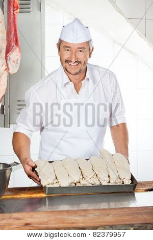 Portrait of confident mature butcher holding tray filled with dredge chicken in shop