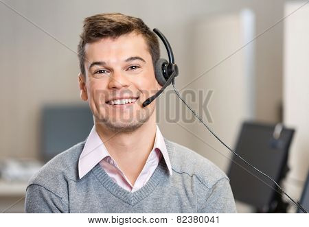 Portrait of confident male customer service representative wearing headset while smiling in office