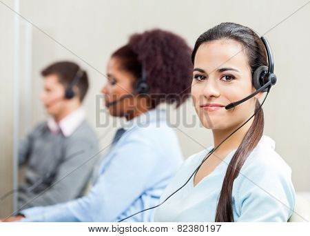 Portrait of confident female customer service representative with colleagues in background at office