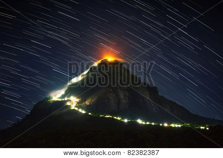 Mountain Adam's Peak (Sri Pada) illuminated at night with starry sky on the background. Sri Lanka