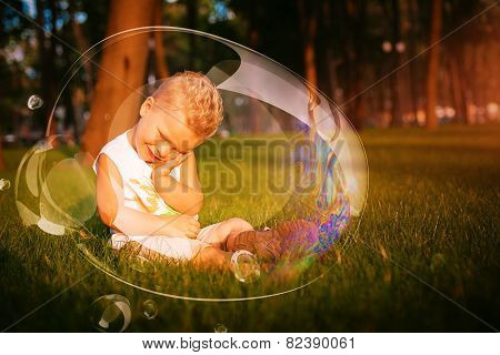 Little Shy Boy Sitting In Grass