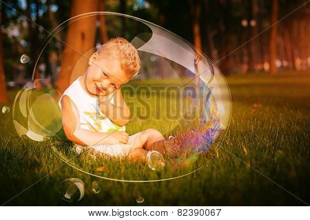 Little Shy Boy Sitting On Grass