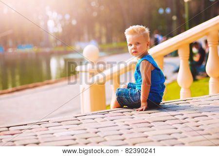 Serious Boy Sitting On Sett Near Balustrade