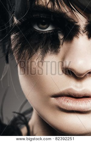 Close Up Portrait Of Woman With Black Feathers On Eye