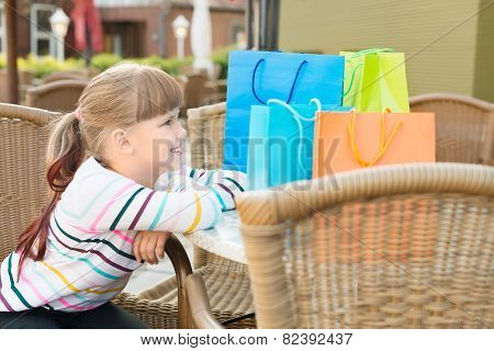Little Girl With Shoping Bags At Outdoor Cafe