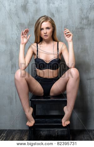 Sexy young blonde woman in black luxury lingerie posing against grungy gray wall. Passion and desire