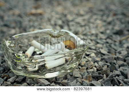 Cigarette In The Ashtray On A Stone Floor.