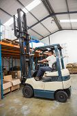 image of forklift driver  - Driver operating forklift machine in a large warehouse - JPG
