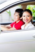 image of driveway  - Asian couple driving new car on driveway to their home - JPG