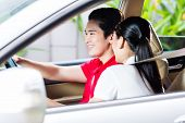 foto of driveway  - Asian couple driving new car on driveway to their home - JPG