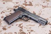picture of camouflage  - old handgun on US Marines camouflage uniform - JPG