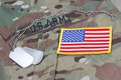 stock photo of camouflage  - us army camouflaged uniform with US flag patch and blank dog tags - JPG