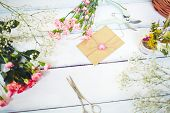 picture of carnation  - Love note in small envelope surrounded by pink carnations on wooden table - JPG