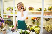 stock photo of flower shop  - Pretty shop assistant speaking on the phone and using laptop in flower shop - JPG
