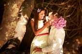 picture of long beach  - brunette bride in long white wedding dress sitting on the big tree and hold her handsome groom on island beach in Thailand - JPG