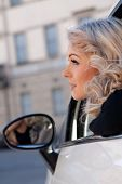 stock photo of tourist-spot  - blonde tourist watches something from her car she - JPG