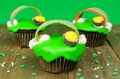 stock photo of pot gold  - St Patricks Day cupcakes with pot of gold and rainbows on wood with green background - JPG