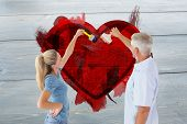 stock photo of wall painting  - Happy couple painting wall with paintbrushes against grey brick wall - JPG