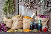 stock photo of mixture  - Healing herbs in hessian bags and bottles of essential oil near rustic wooden wall herbal medicine - JPG