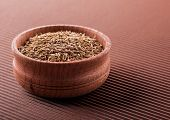image of cumin  - cumin in a wooden bowl on a brown background - JPG