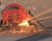 image of cut  - worker cutting deformed bar with cutting machine  - JPG