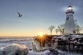 foto of sunrise  - The historic Marblehead Lighthouse in Northwest Ohio sits along the rocky shores of the frozen Lake Erie - JPG