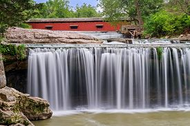 picture of cataracts  - Upper Cataract Falls a scenic waterfall in Indiana is topped by a red historic covered bridge.