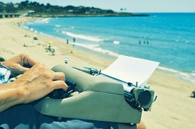 stock photo of old vintage typewriter  - a young man typing in an old typewriter on the beach - JPG