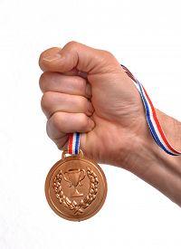 image of gold medal  - Athlete hand holding gold medal - JPG