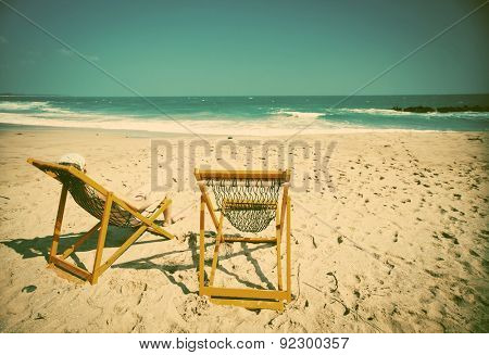Woman in beach chair on a tropical beach - retro style background