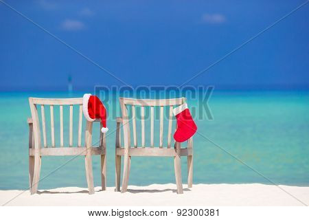 Red Christmas stocking and Santa Hat on chair at tropical white beach