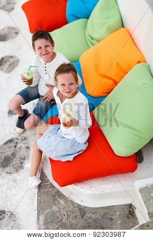 Two cute kids brother and sister drinking fresh smoothies on a colorful pillows at outdoor cafe on summer day