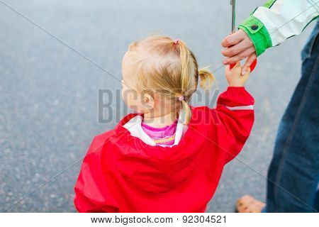 Toddler girl wearing red waterproof coat outdoor on rainy day