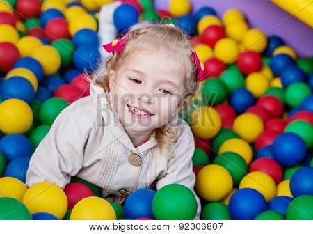 Happy Little Girl Playing On Colorful Balls